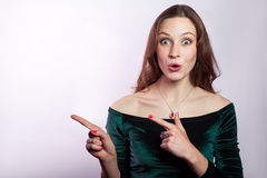 Portrait of surprised shocked woman with freckles and classic green dress showing empty space with finger. Royalty Free Stock Photos