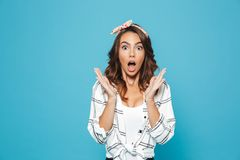 Portrait of surprised or shocked woman 20s wearing casual clothing raising up hands at face, isolated over blue background. Portrait of surprised or shocked royalty free stock photography