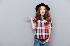 Portrait of a surprised shocked young woman in plaid shirt Stock Photos