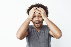 Portrait of surprised and sleepy african man with opened mouth against white wall. Forgot to take a kettle off his stove Stock Photo