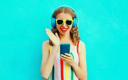Portrait surprised smiling woman holding phone listening to music in wireless headphones on colorful blue stock image
