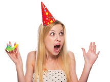 Portrait of surprised teenage girl in cap with party horn blower Royalty Free Stock Images