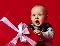 Baby boy with big blue eyes wearing warm sweater sitting in front of his present in wrapped box with ribbon over red background. royalty free stock photos