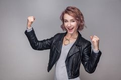 Portrait of surprised winner beautiful girl with short hairstyle, makeup in leather jacket standing, looking at camera and stock photos