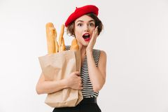 Portrait of a surprised woman wearing beret. Holding paper bag with long loaf isolated over white background Royalty Free Stock Image