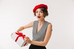 Portrait of a surprised woman wearing red beret. Holding present box isolated over white background Stock Photo