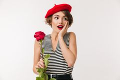 Portrait of a surprised woman wearing red beret. Holding a rose and looking away isolated over white background Royalty Free Stock Photos