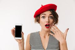 Portrait of a surprised woman wearing red beret. Showing blank screen mobile phone isolated over white background Stock Images