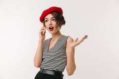 Portrait of a surprised woman wearing red beret. Talking on mobile phone isolated over white background Royalty Free Stock Photos