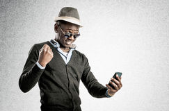 Portrait of surprised young african guy looking at cell phone. Portrait of surprised african guy looking at cell phone Stock Image
