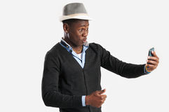 Portrait of surprised young african guy looking at cell phone. Portrait of surprised african guy looking at cell phone Royalty Free Stock Photo