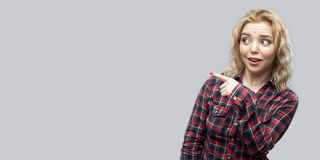 Portrait of surprised young beautiful blonde woman in casual red checkered shirt standing looking and pointing at copyspace royalty free stock photos