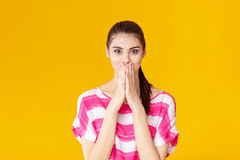 Portrait of surprised young brunette woman in pink shirt on yellow background. girl looks at camera Stock Photos