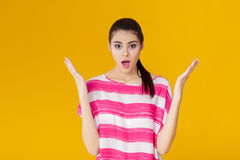 Portrait of surprised young brunette woman in pink shirt on yellow background. girl looks at camera. Portrait of surprised young brunette woman in pink shirt on Royalty Free Stock Photos