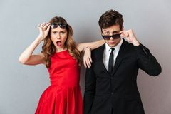 Portrait of a surprised young couple dressed in formal wear. And sunglasses posing while standing and looking at camera over gray wall background Royalty Free Stock Photos