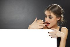 Surprised young girl holding blank billboard Stock Photo