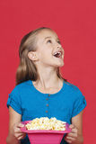 Portrait of surprised young girl holding popcorn container against red background Stock Photo