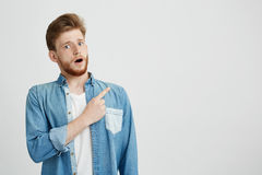 Portrait of surprised young handsome man looking at camera with opened mouth pointing finger up over white background. Stock Photos