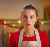 Portrait of surprised young housewife in christmas kitchen Stock Photography