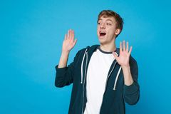 Portrait of surprised young man in casual clothes looking aside, rising hands, keeping mouth open isolated on blue. Background in studio. People sincere stock photo