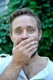 Portrait of a surprised young man covering his mouth with hand. Outdoor Royalty Free Stock Image
