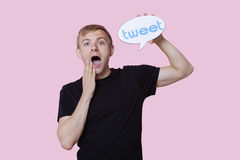 Portrait of surprised young man holding tweet bubble against pink background Royalty Free Stock Images