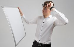 Portrait of surprised young man wearing glasses with clean magnetic Board isolated on white background. Stylish Young man lifted his glasses and looks at white stock photo