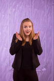 Portrait of a surprised young woman in a black suit Royalty Free Stock Photography