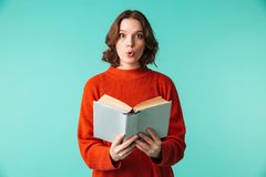 Portrait of a surprised young woman dressed in sweater. Holding book isolated over blue background Royalty Free Stock Photo