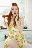 Portrait of a surprised young woman with hair tangled in whisk sitting on kitchen counter Royalty Free Stock Images