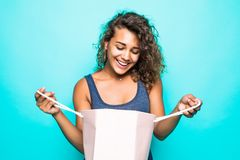 Portrait of a surprised young woman opening shopping bags standing over green background stock photo