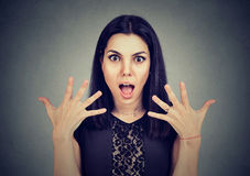 Portrait of a surprised young woman with wide open mouth and hands up in air Royalty Free Stock Images