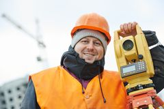 Portrait of surveyor worker with theodolite. Surveyor worker portrait with theodolite transit equipment at road construction site outdoors Royalty Free Stock Images