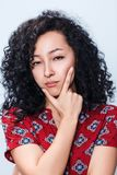 Portrait of suspicious young woman. Portrait of suspicious young woman with curly black hair over blue background Royalty Free Stock Image