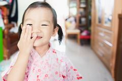 Sweet Asian little child smile, shy and covering her face. Portrait of Sweet Asian little child smile, shy and covering her face royalty free stock images