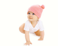 Portrait of sweet baby crawls in the pink knitted hat Royalty Free Stock Photos