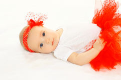 Portrait of sweet baby girl in the red skirt. Portrait of sweet baby girl lying in the red skirt Royalty Free Stock Photography