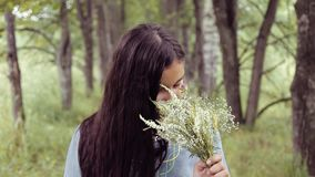 Portrait. A sweet beautiful little girl is sniffing a bouquet of flowers standing on nature in a summer sunny day while. Portrait. A nice beautiful little girl stock video