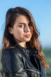 Portrait of sweet Brunette girl in leather jacket looking at the Stock Photo