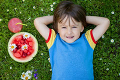 Portrait of sweet little boy, lying on the grass, fresh fruits a Royalty Free Stock Photography