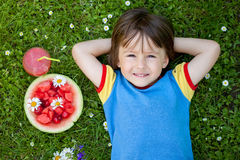 Portrait of sweet little boy, lying on the grass, fresh fruits a Stock Photography