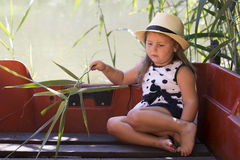 Portrait of sweet little girl in a dress with a hat while sittin. G in a boat on the lake. She plays and loves to spend time in nature, enjoying the beautiful Royalty Free Stock Photo