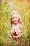 Portrait of sweet little girl. Outdoors sitting and hiding in grass stock photography