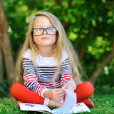 Portrait of sweet little girl wearing glasses, reading book, sit. Ting at summer green park Royalty Free Stock Photos