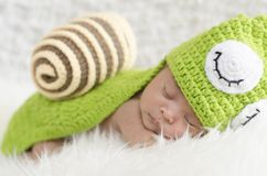 Portrait of sweet newborn baby in knitted snail costume. Sleeping on white blanket.selective focus shot Stock Images