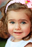 Portrait of a sweet one year old girl with pink head band with bow and flower in the summer park with expression of surpr Stock Photos