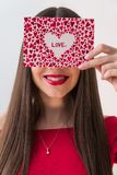 Portrait of a sweet perfect girl smiling at camera with heart shaped paper in her hands. Valentine`s Day or Women`s Day royalty free stock images