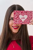 Portrait of a sweet perfect girl smiling at camera with heart shaped paper in her hands. Valentine`s Day or Women`s Day. Concept Royalty Free Stock Photography