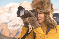 Portrait of a sweet tourist girl in a big fur hat takes pictures on her digital camera in the mountains. Portrait of a sweet tourist girl in a big fur hat takes Royalty Free Stock Photos