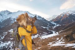 Portrait of a sweet tourist girl in a big fur hat takes pictures on her digital camera in the mountains. Portrait of a sweet tourist girl in a big fur hat takes Royalty Free Stock Image